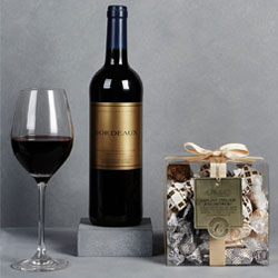 A bottle of bordeaux red wine and italian chocolate assortment