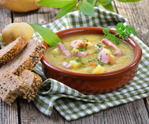 Rich German Pea Soup served with meat sausage and bread