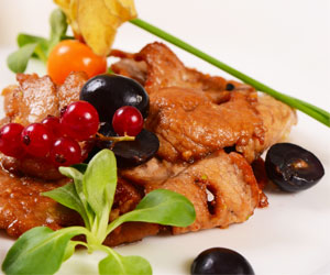 Chicken with red pesto, grapes and wine sauce on watercress